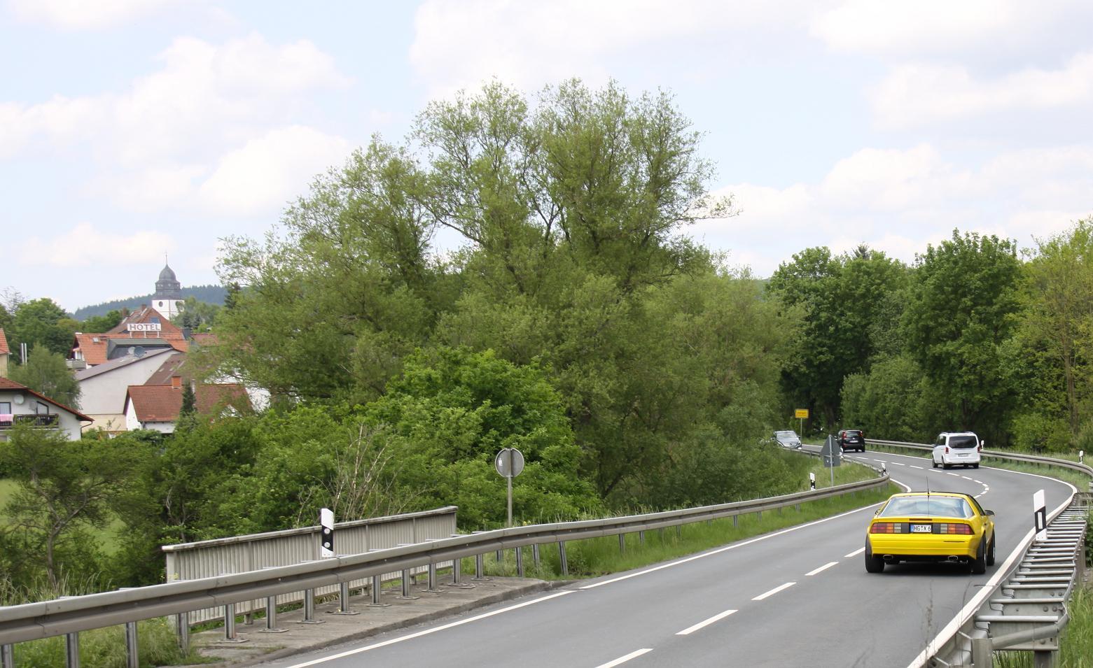 Der Camaro etwa hundert Meter vor der Eingangskontrolle. Weiter vorne wird der Kirchturm von Bäumen verdeckt.