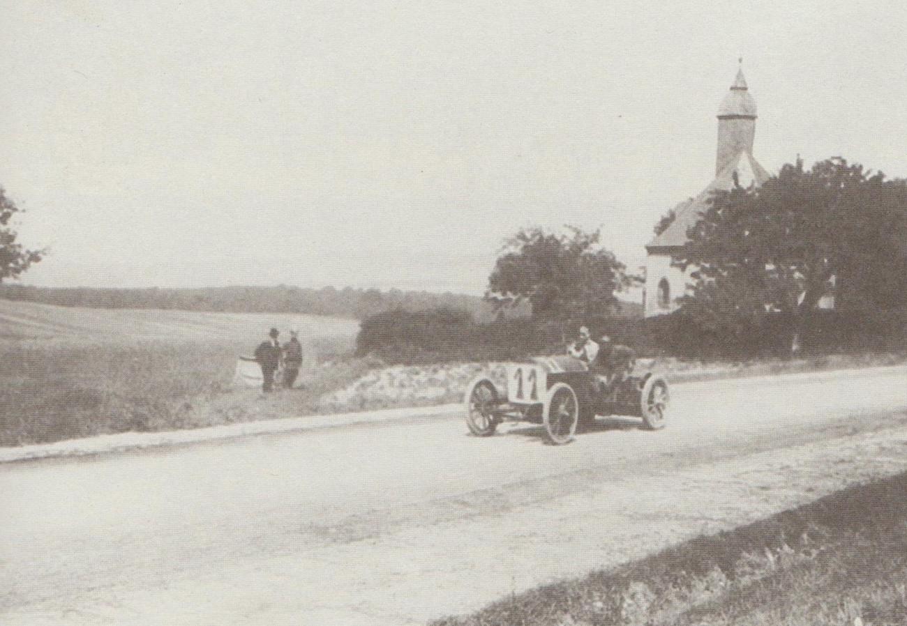 Luigi Storero mit seinem FIAT in voller Fahrt an der Glashüttener Kirche, unterwegs für das italienische Team. Italiens Rennwagenfarbe war übrigens damals Schwarz.