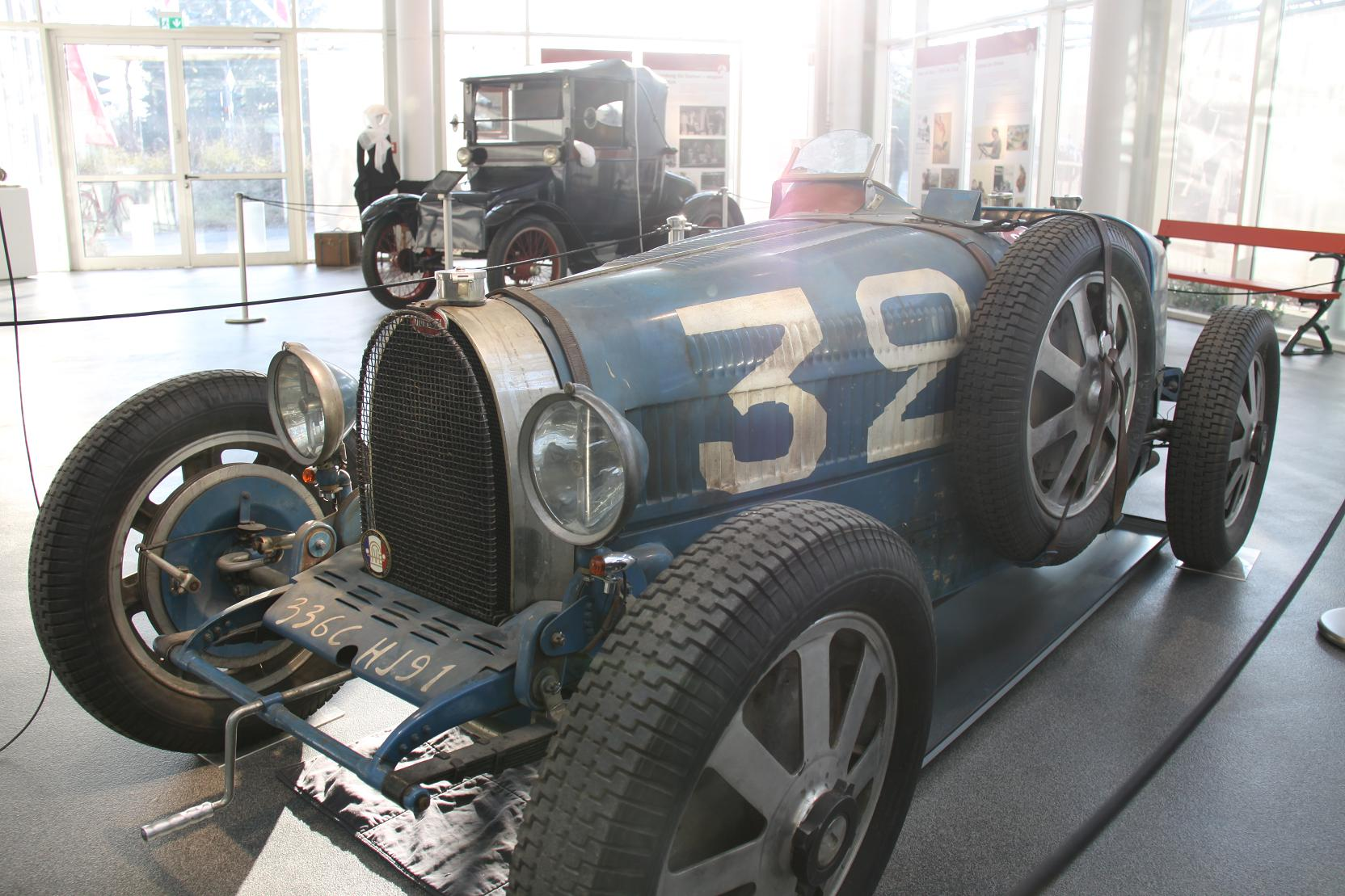 Elisabeth Junek teilte die Leidenschaft für Bugatti mit ihrem Mann Vincenz. Zeitweise besaß das Paar drei Bugattis, mit denen sie bei Berg- und Rundstreckenrennen siegreich waren. Übrigens: im Hintergrund ein Detroit Electric von 1909 – die Idee des Elektroautos ist gar nicht so neu.